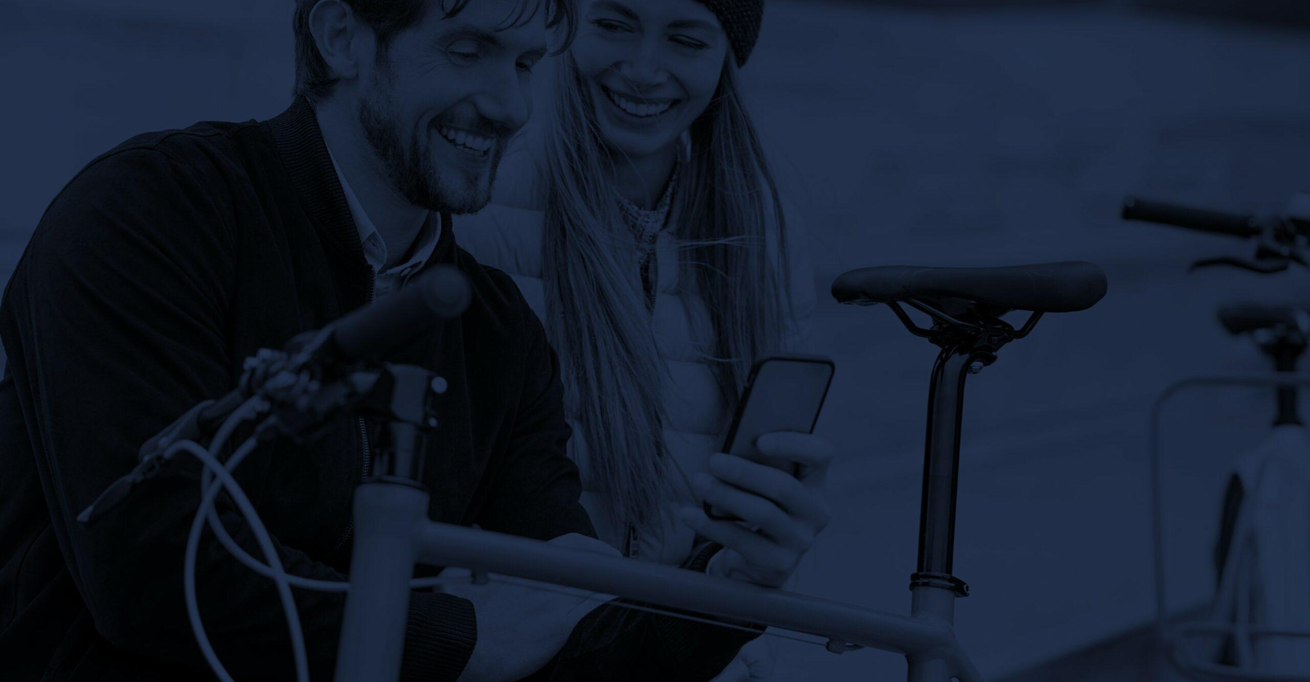 Pärchen sitzt auf einer Parkbank mit einem Fahrrad im Vordergrund