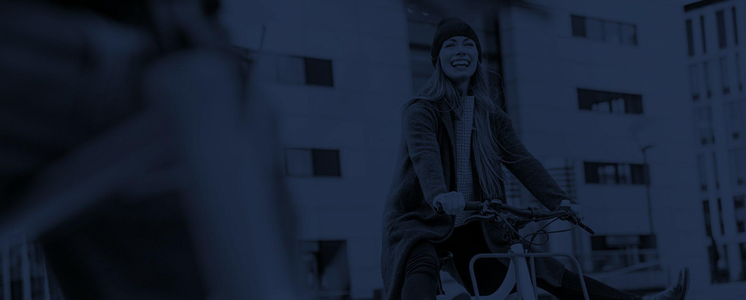 Eine Fahrradfahrerin hebt die Beine vom Fahrrad hoch und lacht in die Kamera.